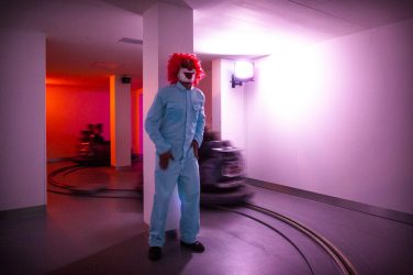 a clown stands in a pink room at Phobiarama